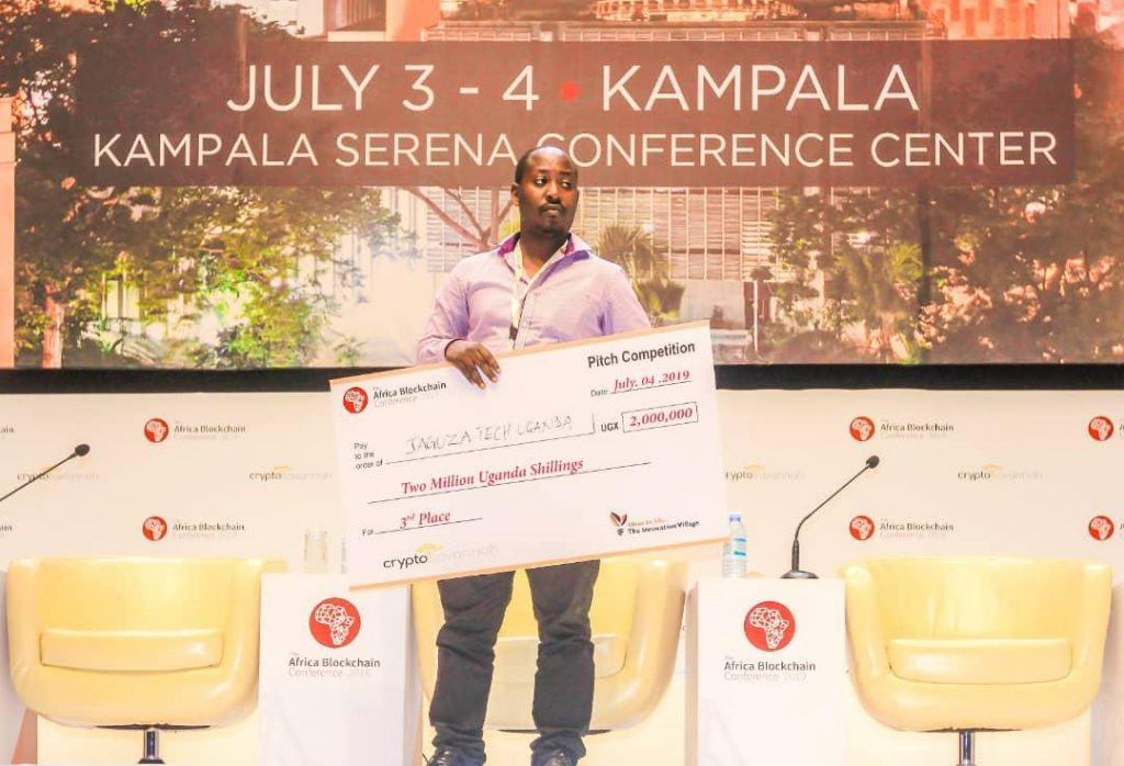 Jaguza Tech Founder; Ronald Katamba holds a dummy $2,000 cheque won in the Africa Blockchain pitch competition. Photo by/ Olupot Nathan Ernest