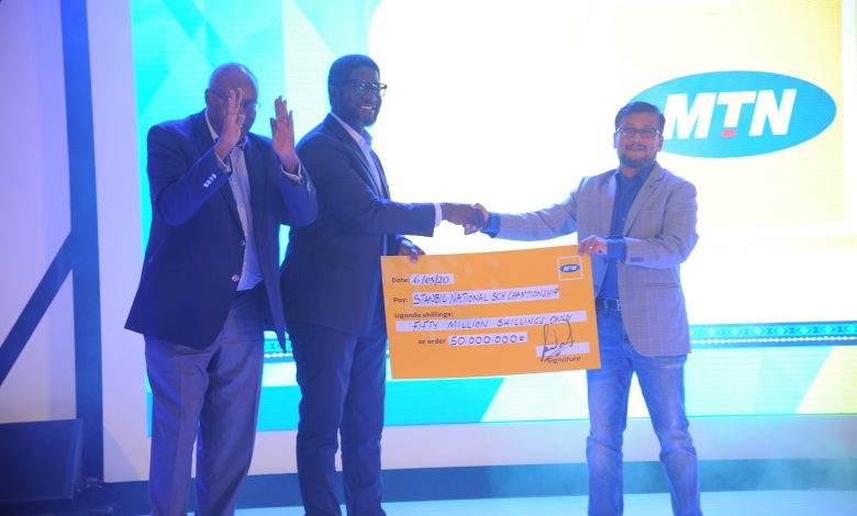 Mr. Sem Somdev, MTN Uganda's Chief Marketing Officer (left) handing over a cheque of UGX50 million to Stanbic Bank Uganda for the National School Championship. File Photo
