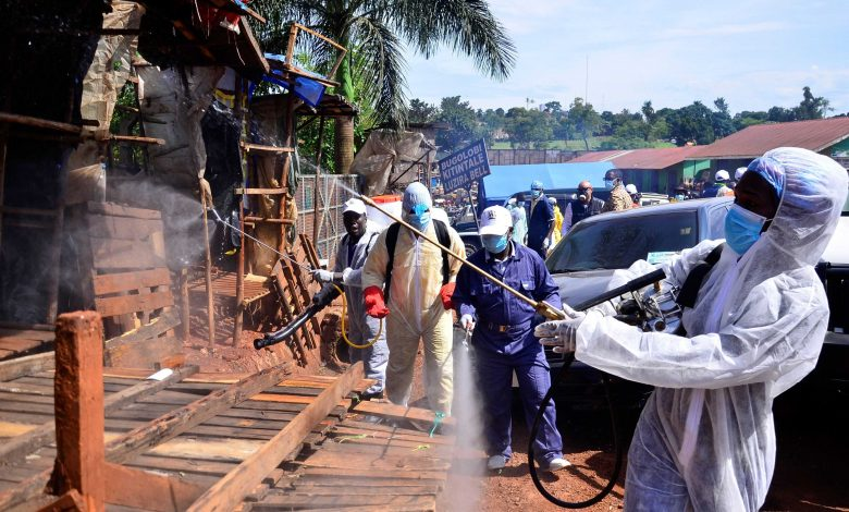 FILE - Ugandan health officials wearing protective gear disinfect the Nakawa open-air market as part of the measures to prevent the spread of the COVID-19, in Nakawa division of Kampala, April 17, 2020. (Courtesy Photo)