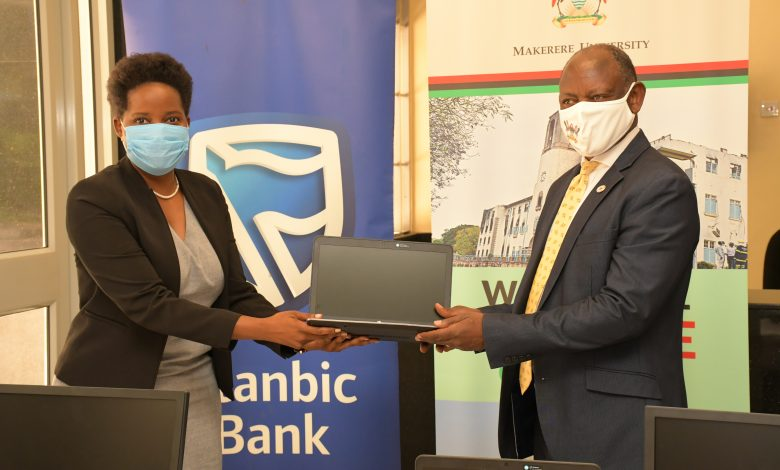 Ms. Anne Juuko; the Chief Executive Officer of Stanbic Bank Uganda handing over the computers to the Vice Chancellor Makerere University; Prof Barnabas Nawangwe. Courtesy Photo