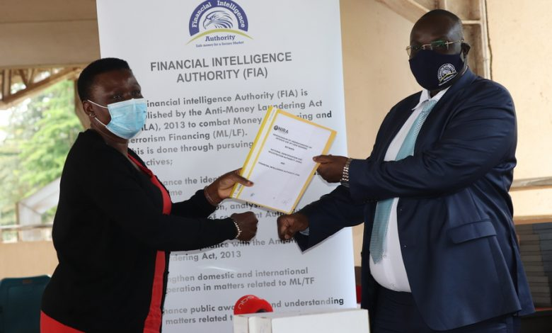 NIRA Agatha Mutenyo and FIA Sydney Asubo show off the signed MoU. Courtesy Photo