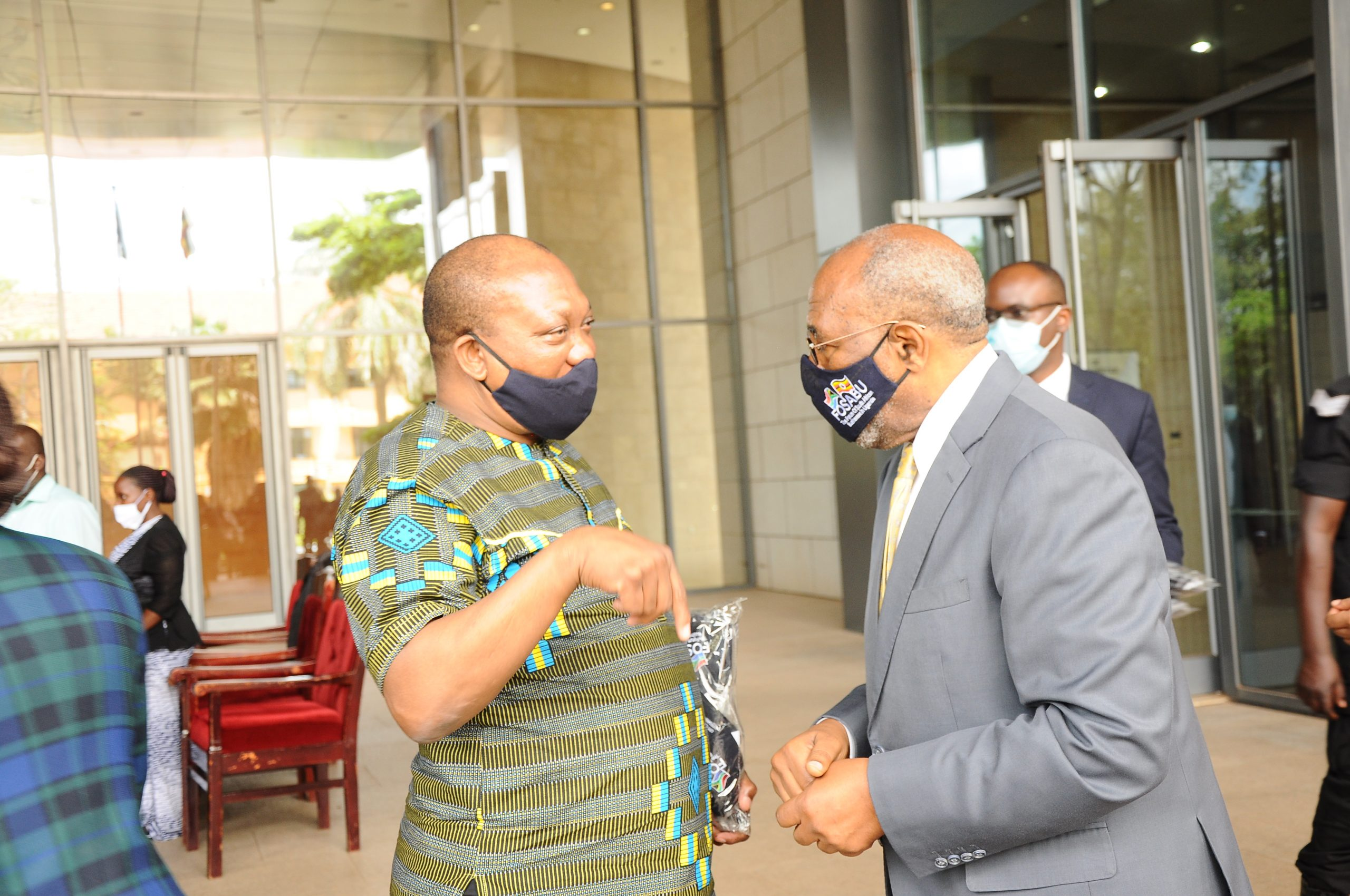 South African High Commissioner Lekoa Solly Mollo with the Prime Minister to Uganda Ruhakana Rugunda have a chat after FOSABU handed over Covid-19 PPE worth UGX100 million.
