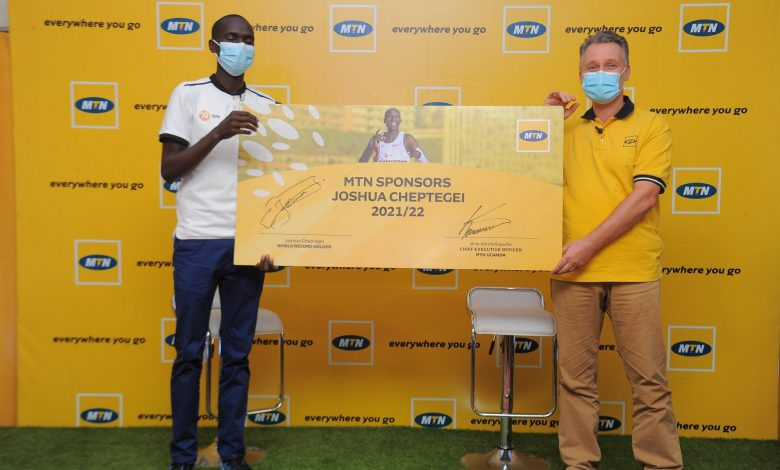 World record breaking athlete, Joshua Cheptegei (L) and MTN Uganda Chief Executive Officer, Wim Vanhelleputte (R) hold a sponsorship card after announcing a sponsorship deal at the Mbale Resort Hotel on Saturday 20th, February 2021 (COURTESY PHOTO/MTN Uganda)