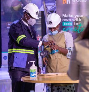 One of the beneficiary of the Tools to Create Facility demonstrating to Aggrey Kibenge (L) how one of the tools work, after he officially launched the facility. (COURTESY PHOTO)