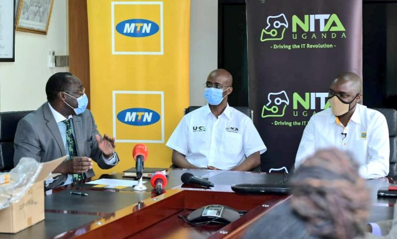 Dr. Okware Joseph speaking to NITA-Uganda Executive Director, Dr. Hatwib Mugasa (c) and MTN Uganda General Manager for MTN Business, Mr. Ibrahim Ssenyonga (r) at the launch of the E-Pass app on Friday at the Ministry of Health head offices in Kampala. (COURTESY PHOTO)