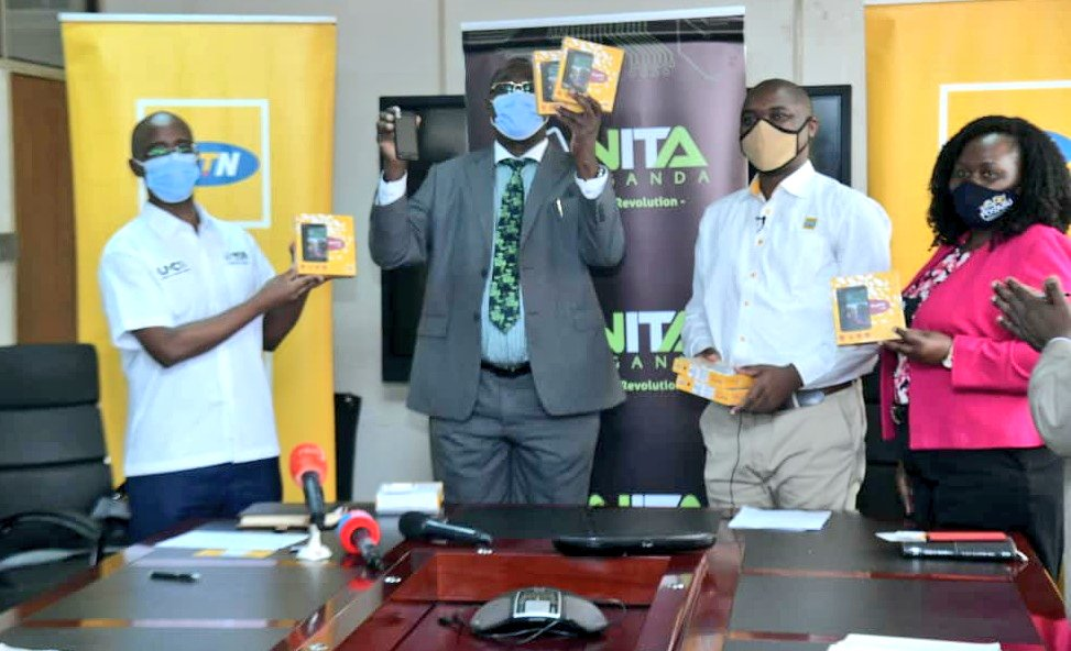Dr. Okware Joseph (2nd from left) displays the phones handed over to the Ministry of Health while NITA-Uganda Executive Director, Dr. Hatwib Mugasa (extreme left, MTN Uganda General Manager for MTN Business, Mr. Ibrahim Ssenyonga (2nd from right) and MTN Uganda General Manager Corporate Services, Ms. Enid Edroma look on. (COURTESY PHOTO)