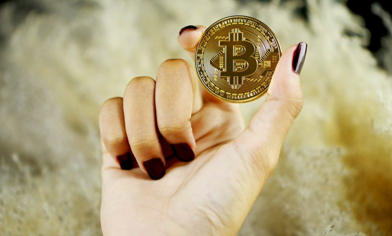 A woman holding a Bitcoin which has become a popular means of transferring funds over the internet, and it is especially beneficial for international payments. (Photo by Executium on Unsplash)